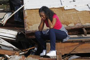 A woman sobs amid the wreckage of her home