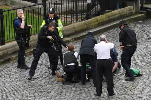 Police surround the knifeman as he lies on the ground in the cobbled courtyard in front of Parliament