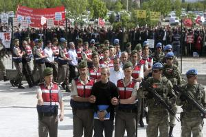 Paramilitary police officers and commandos escort the alleged instigators of last summer's coup
