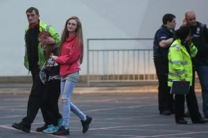 A girl is hugged as she leaves Manchester Royal Infirmary in tears