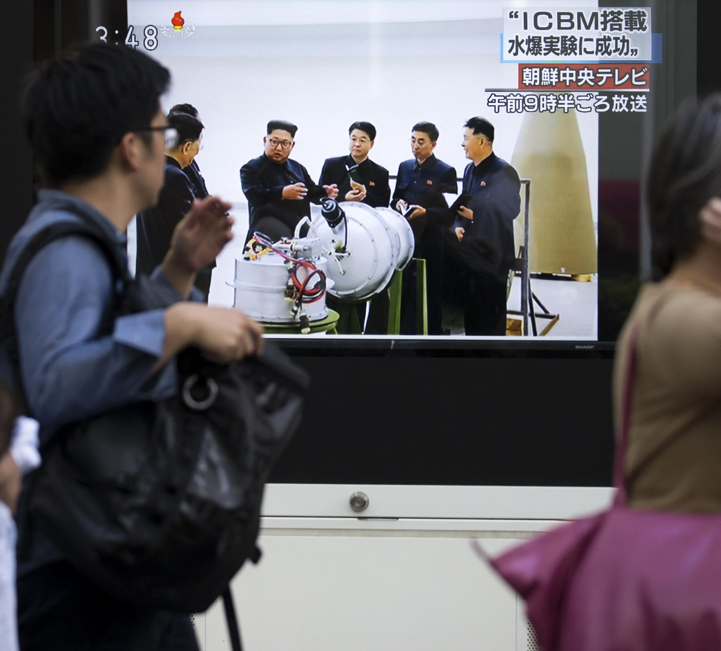 People walk past a monitor showing news footage of North Korea's sixth nuclear test