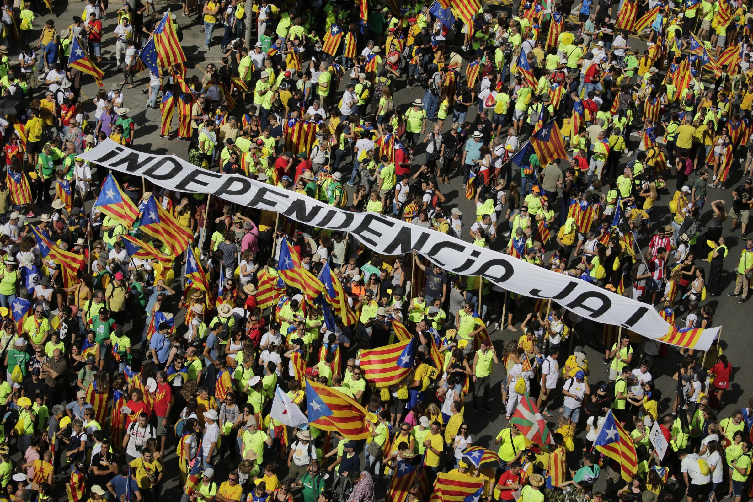 People hold a banner reading 'Independence now' as they mark Catalonia's National Day