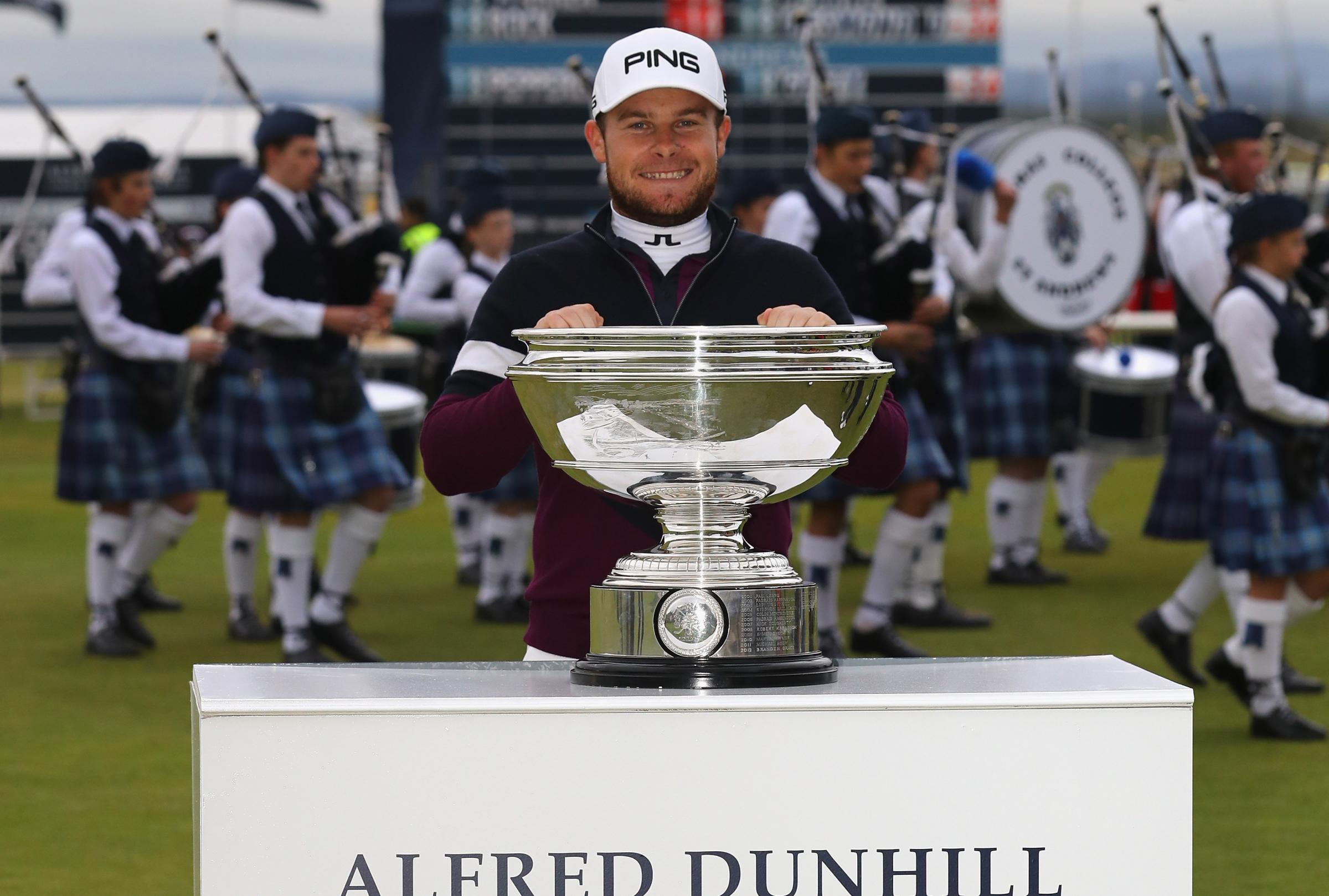 Tyrrell Hatton celebrates victory with the trophy following the final round of the 2017 Alfred Dunhill Championship