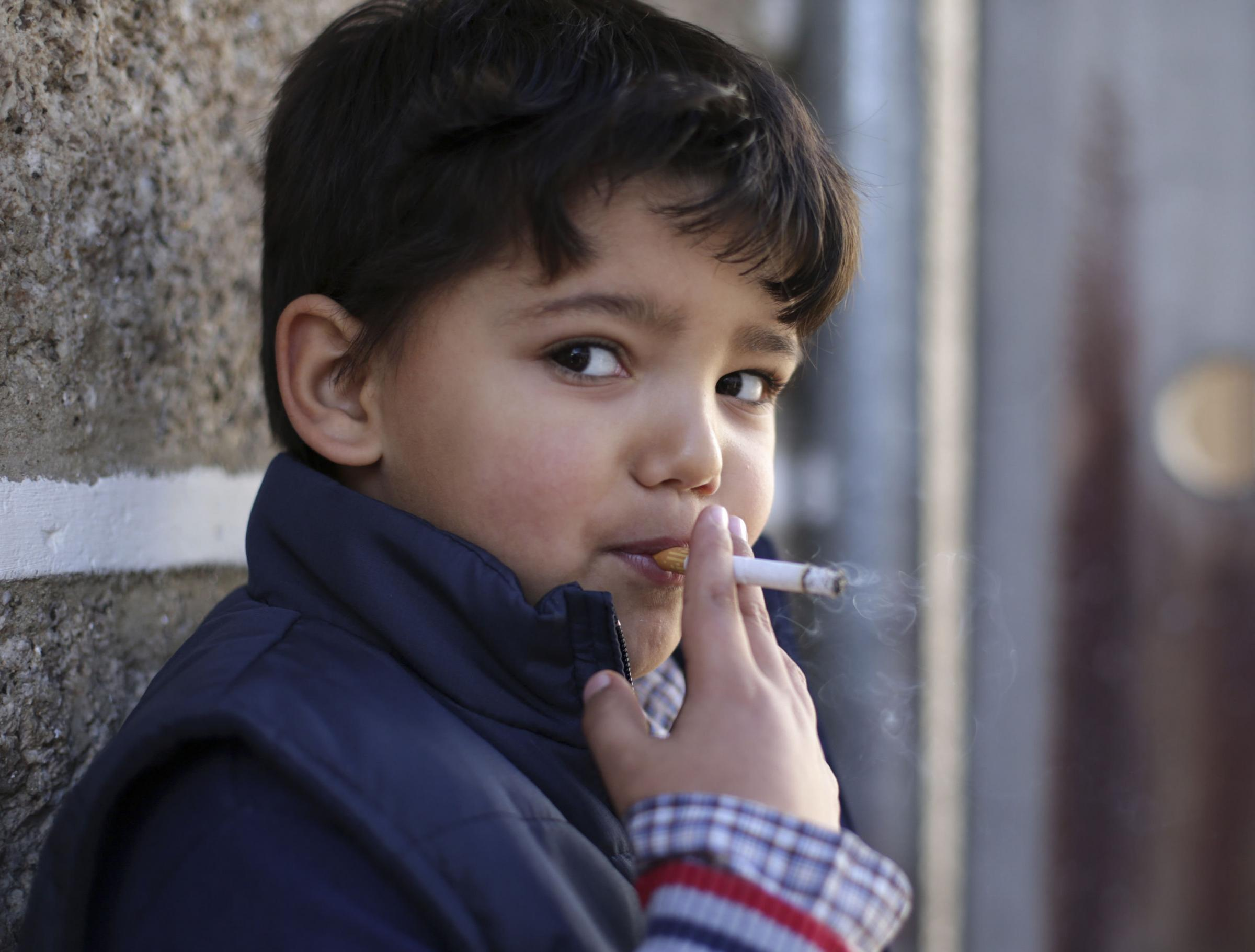 Fernando, 6-years-old, smokes a cigarette in the village of Vale de Salgueiro, northern Portugal, during the local Kings' Feast Saturday, Jan. 6, 2018. The village's Epiphany celebrations, called Kings' Feast, feature a tradition that each yea