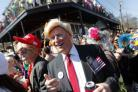 John Shreves, centre, of New Orleans, runs into Jeff Jones, right, who both dressed as Donald Trump, during the Society de Sainte Anne parade, on Mardi Gras day in New Orleans, Tuesday, Feb. 13, 2018
