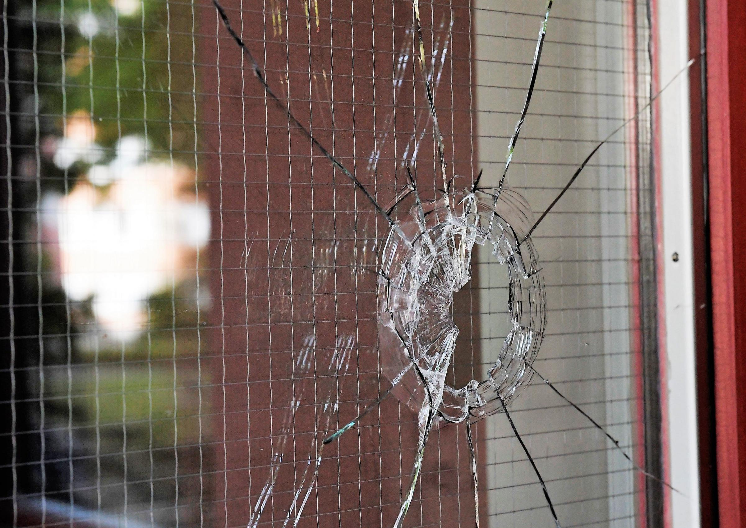 A hole in a glass door at the site where Eric Torrel was shot and killed by police